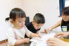 1-year-old Japanese girl and 2-year-old boy drawing pictures with mother Stock Photo