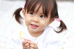Japanese girl eating an apple. (1 year old royalty free stock images