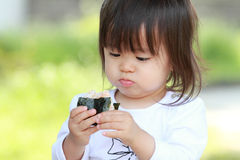 Japanese girl eating rice ball. (1 year old Stock Image