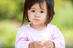 Japanese girl eating rice cracker. (1 year old royalty free stock image