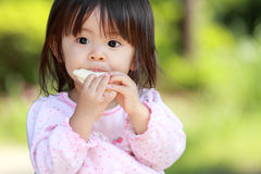 Japanese girl eating rice cracker. (1 year old royalty free stock photos