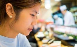 Japanese Girl eating Sushi roll Royalty Free Stock Image