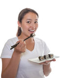 Japanese girl eating sushi. Smiling japanese girl eating fresh sushi rolls with sticks royalty free stock photos