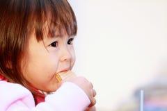 Japanese girl eating wafers Stock Photos