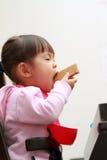 Japanese girl eating wafers Royalty Free Stock Image