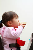 Japanese girl eating wafers Stock Images