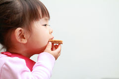 Japanese girl eating wafers Stock Photography