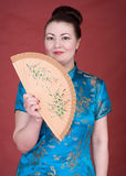 Japanese girl with fan. On the red background Royalty Free Stock Image