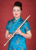 Japanese girl with flute. On the red background Stock Photos