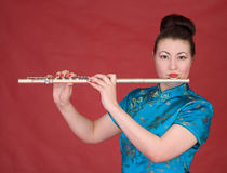 Japanese girl with flute. On the red background Royalty Free Stock Photos
