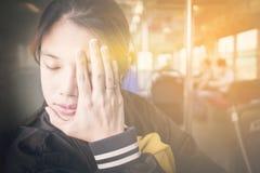 Japanese girl having a bad headache on a train Royalty Free Stock Photos