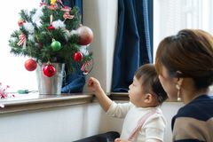 Japanese woman and girl decorating Christmas tree by window in living room Stock Photo