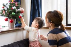 1-year-old girl and mother decorating Christmas tree Royalty Free Stock Photo