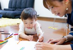1-year-old girl drawing picture with mother stock photo