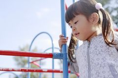 Japanese girl on the jungle gym. 4 years old royalty free stock photo