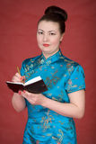 Japanese girl with notebook. On the red background Stock Photos