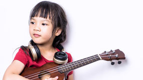 Japanese girl is playing guitar and wearing headphone. Little Asian artist looking firm and confidence with her music instrument. Little asian musician with stock photography