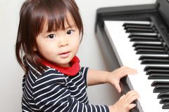 Japanese girl playing a piano. 2 years old stock images