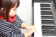 Japanese girl playing a piano. 2 years old royalty free stock image