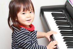 Japanese girl playing a piano. 2 years old stock photo