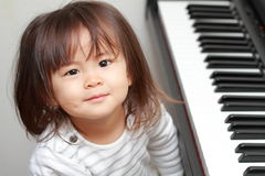 Japanese girl playing a piano. 2 years old royalty free stock photos