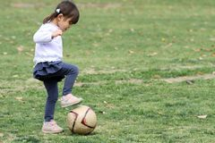 Japanese girl playing with soccer ball. 3 years old stock photo