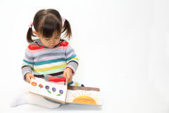 Japanese girl reading a picture book. 2 years old stock photos