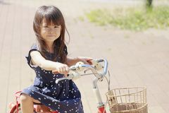 Japanese girl riding on the bicycle. 4 years old stock image