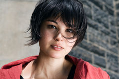 Japanese girl with short hair with freckles. Closeup portrait of a beautiful young asian Japanese girl with freckles with black short pixie haircut in red shawl royalty free stock image