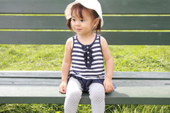 Japanese girl sitting on the bench in the field. (1 year old royalty free stock photography