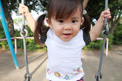 Japanese girl on the swing. 2 years old stock photos
