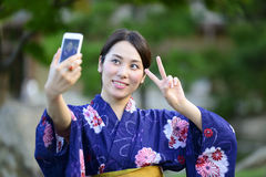 Japanese girl taking a self portrait. With smart phone Stock Photos