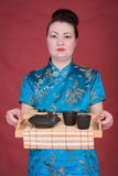 Japanese girl with tea-tray. On the red background Stock Image