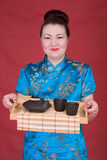 Japanese girl with teapot. On the red background Royalty Free Stock Photography