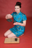 Japanese girl with teapot. On the red background Royalty Free Stock Photos