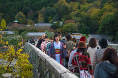 Japanese girl on Togetsukyo bridge, Arashiyama. KYOTO, JAPAN - NOVEMBER 12, 2015: Unidentified Japanese girl with traditional Kimono dress walking on Togetsukyo royalty free stock image
