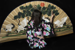Japanese girl in traditional Japanese kimono with a large fan on Royalty Free Stock Photography