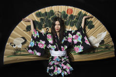 Japanese girl in traditional Japanese kimono with a large fan on Stock Photo