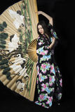 Japanese girl in traditional Japanese kimono with a large fan on Royalty Free Stock Image