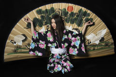 Japanese girl in traditional Japanese kimono with a large fan on Royalty Free Stock Images