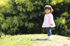 Japanese girl walking on the grass Stock Images
