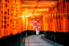 Japanese girl in Yukata with red umbrella at Fushimi Inari Shrine. In Kyoto, Japan royalty free stock photo