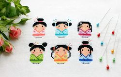 Japanese girls embroidered on the fabric, decorated with pins and pink roses stock photos