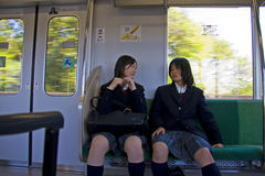 Japanese girls railway train coach. Two Japanese girls talking in the railway train coach on their way to school Royalty Free Stock Photos