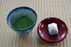 Japanese green tea and cake. A closeup of a bowl of Japanese green tea prepared in the traditional tea ceremony served with a small pieces of traditional cake royalty free stock photos