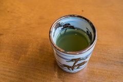 Japanese green tea in cup on wood background.  Stock Photo