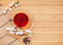 Japanese green tea and sakura branch over mat and bamboo table Royalty Free Stock Images