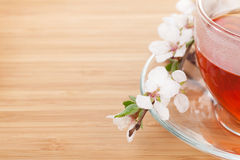 Japanese green tea and sakura branch over mat and bamboo table Stock Photo
