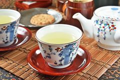 Japanese green tea and teapot. On bamboo mat royalty free stock images