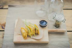 Japanese guiozas with soya sauce on wooden chopping table Royalty Free Stock Image